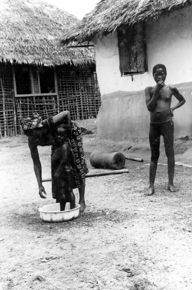 Photo: Woman bathes baby in enamel bowl, preadolescent child stands nearby. Houses, mortar, pestles behind.