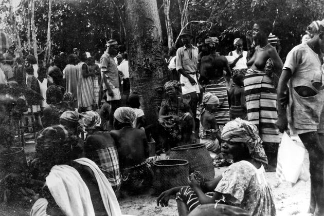 Photo: Liberian group in village on market day. Women seated with baskets under tree at center.
