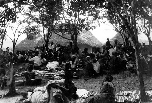 Photo: Liberian group in village. Men seated on cloths spread on ground in foreground. Houses behind.