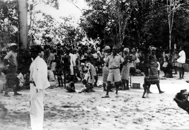 Photo: Liberian group in village. Most people in this image are standing or walking except for two sitting children.