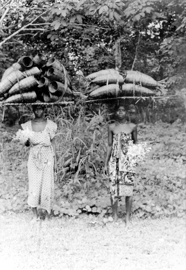 Photo: Two women carrying crawfish traps on their heads, and holding bouquets of flowers.