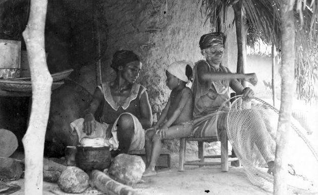 Photo: Two women and a child seated in front of a house. Younger woman tends a cooking pot while the older woman makes a large flat basket, shares stool with child.