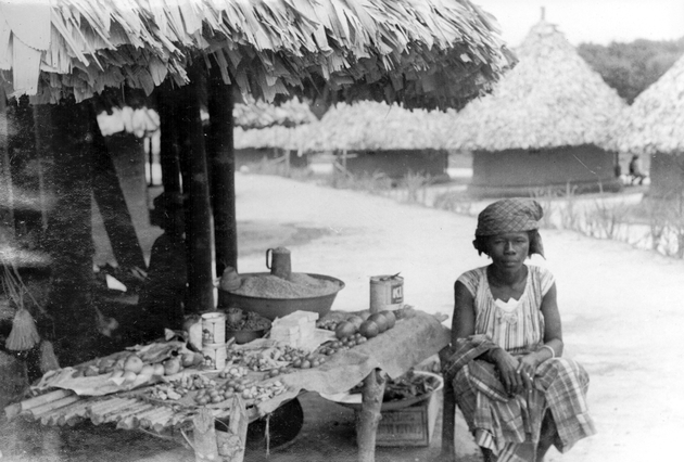 Photo: Liberian woman tends a market stall in village or work camp. She has bitter ball, cola and rice among other things for sale.