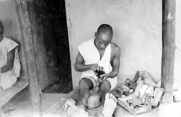 Photo: Seated man at work, perhaps making shoes. He has a kit of leather material at his side.