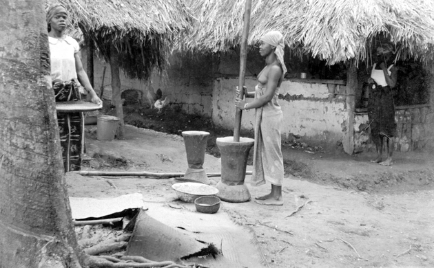 Photo: Young Liberian woman pounds grain in front of house. Two women stand behind, one with winnowing basket.