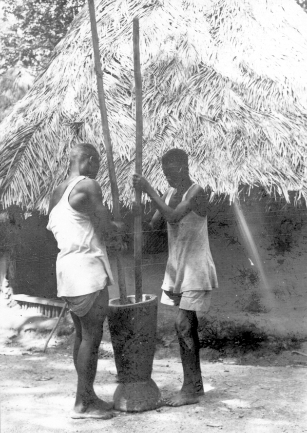 Photo: Two Liberian men using a mortar, each with a pestle.