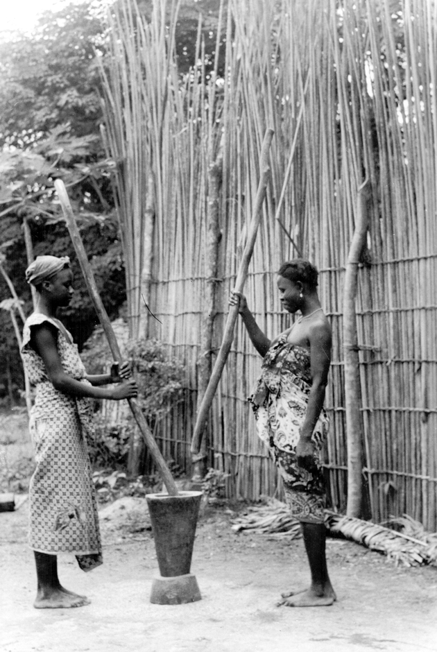 Photo: Two Liberian women using a mortar, each with a pestle. They are posed in front of a reed or bamboo fence.