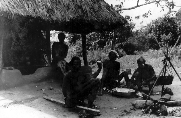 Photo: Four Liberian adult men eat cassava from a bowl. Cooking fire with pot suspended from tripod is nearby. Underexposed image.