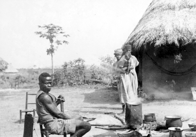 Photo: Two Liberian men and a woman holding an infant surround a cooking fire with several metal pots.