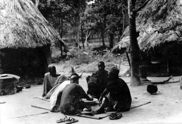 Photo: Five Liberian men sit on a mat around a bowl. Two houses, a cooking pot, sandals are nearby.