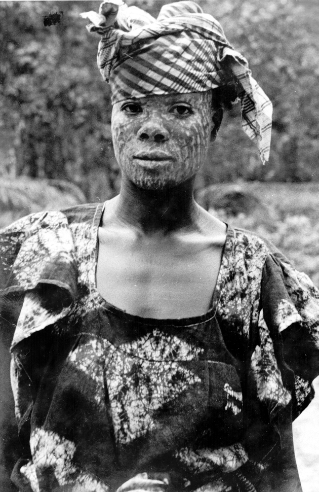Photo: Portrait of Liberian woman in batik dress with plaid headscarf. She wears chalk on her face, which is worn for Sande Society initiation ceremonies and as a traditional cure.