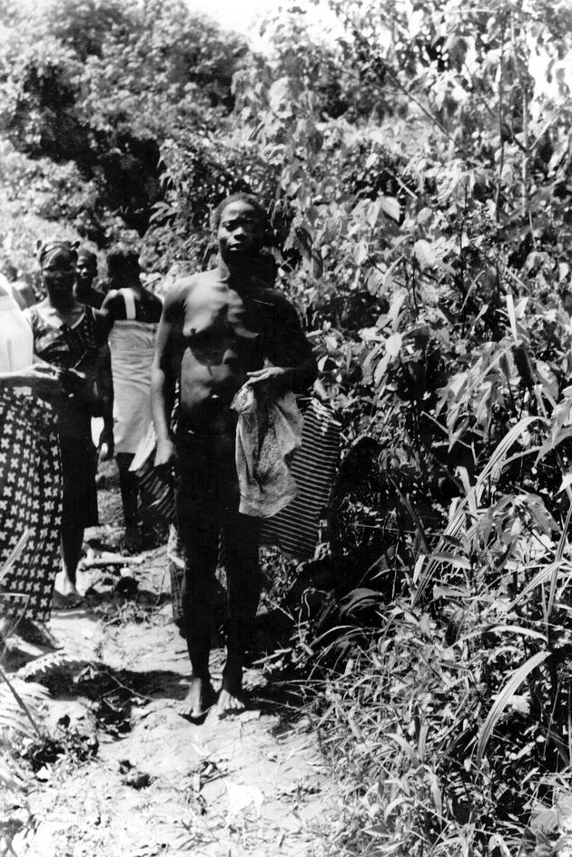 Photo: Liberian man posing along a path in the bush, with several women standing in background.