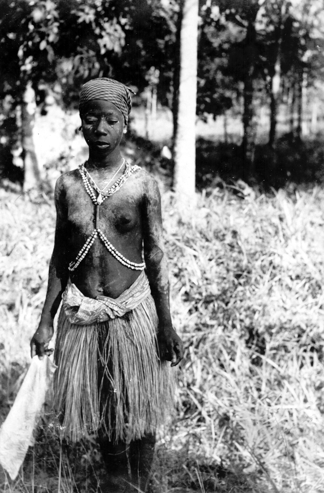Photo: Adolescent girl in ceremonial dress. She may be dressed for a Sande initiation ceremony.