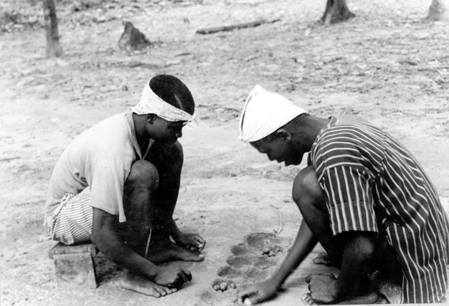 "Photo: Two seated Liberian men playing Mancala or ""Poo"" with pebbles or seeds placed in holes in the ground."