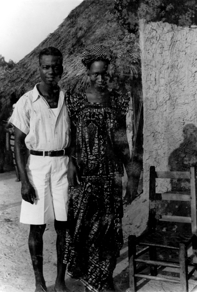 Photo: Liberian man and woman pose standing up for portrait in front of a house.