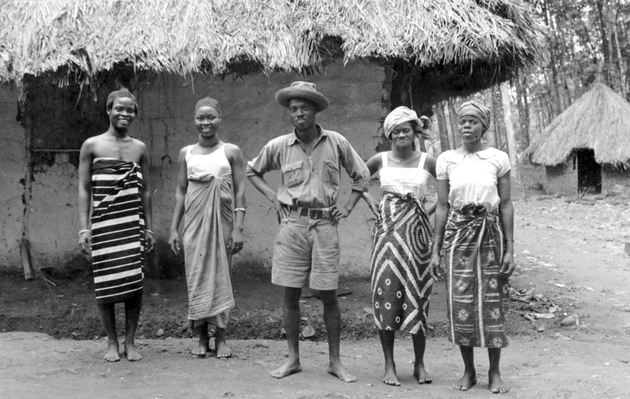 Photo: Liberian man standing with two young women and two older women in front of a house. Possibly the women are this man's wives?