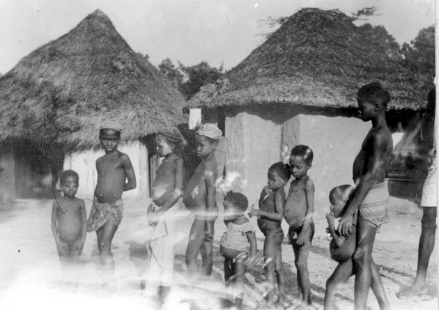 Photo: A group of nine children in the village. Small photo is damaged in lower left.