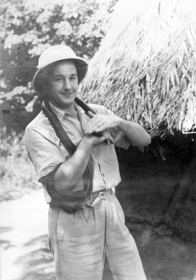 Photo: American man in short khakis and pith helmet handles a large snake.