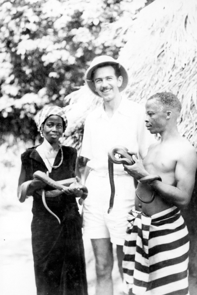 Photo: Manis poses with a Liberian man and woman, each of whom holds a snake.