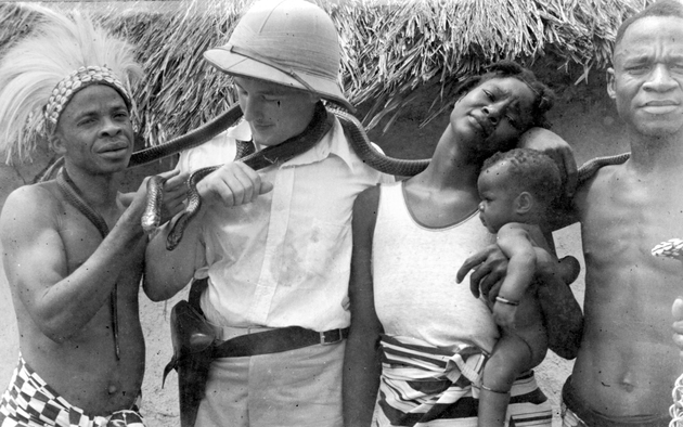 Photo: American man in pith helmet and with a holstered pistol poses with several Liberians handling two large snakes.