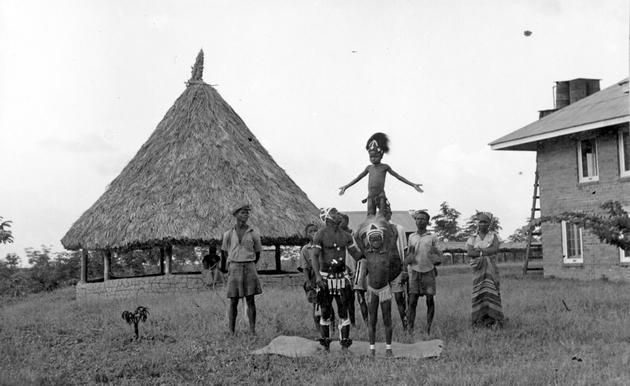 Photo: Acrobatic performance with child standing on adult's shoulders. African and Western style buildings behind.