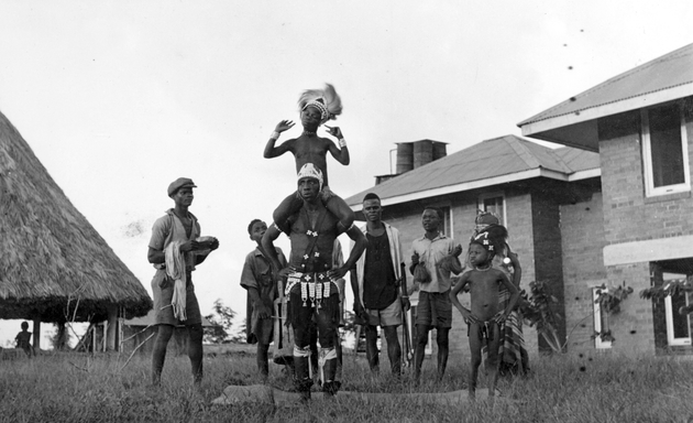 Photo: Acrobatic performance with child sitting on adult's shoulders. African and Western style buildings behind.