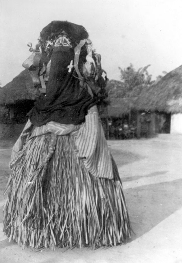 Photo: A masked and costumed dancer. Thatched buildings are visible in background.