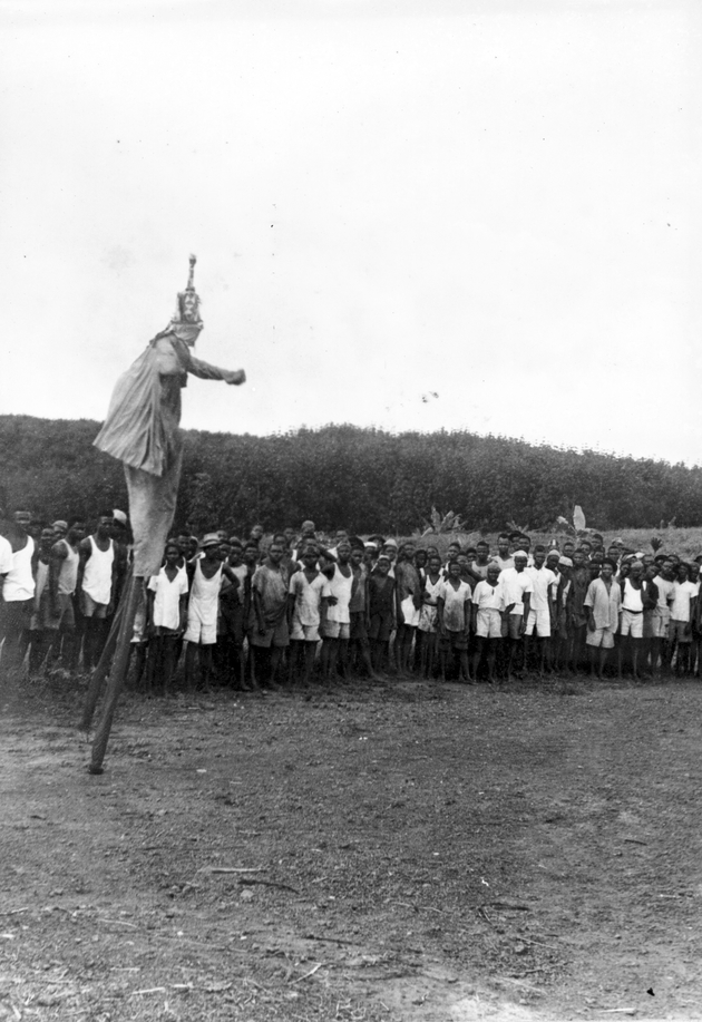 Photo: Masked dancer performs on tall stilts in front of a large audience of more than 70 young men.