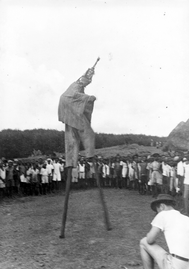 Photo: Masked dancer performs on tall stilts. An American squats in the foreground.