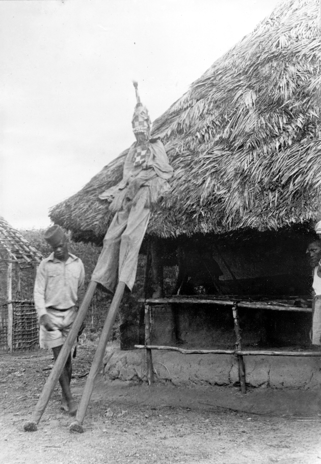 Photo: Masked dancer on stilts, resting against a thatched roof.