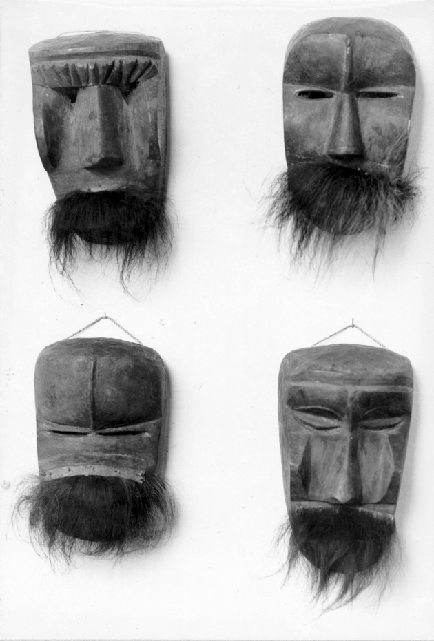 Photo: Four bearded or mustached masks appear to be suspended from nails on a white wall.