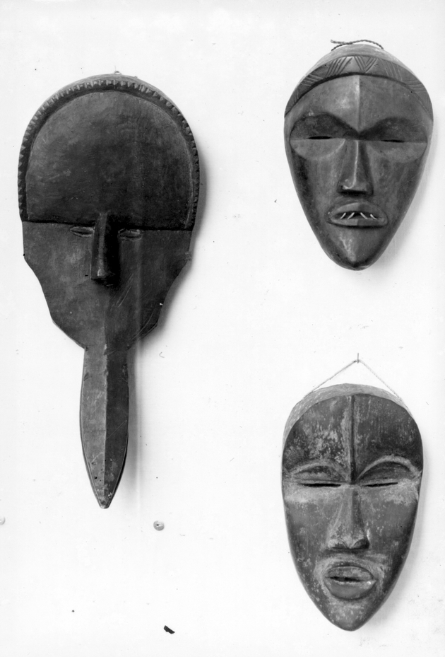 Photo: Three masks, one with a long beak, another with four sharp metallic teeth, are suspended on a white wall.