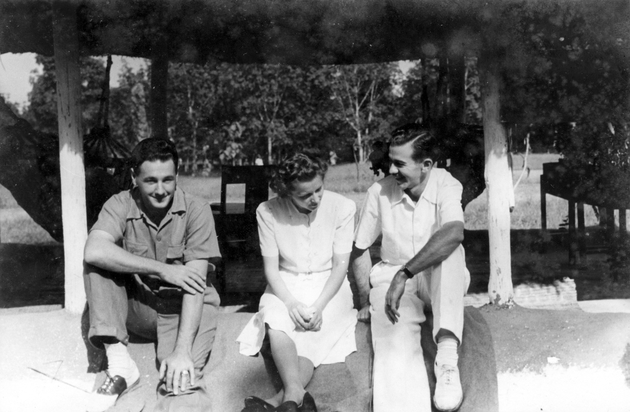 Photograph: Two American men and a woman, seated. Manis is on the right.
