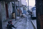 Children sitting on the sidewalk of a busy street in Saint John, Antigua