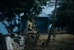 Children beside a zinc roofed house in Jamaica