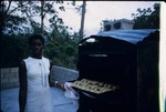 A Jamaican woman baking patties in an outdoor oven