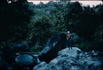 A man standing on river rocks in Jamaica