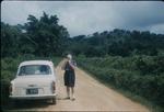 A man standing next to a car on a dirt road in Saint Ann, Jamaica