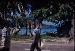 Two men walking and a bauxite plant in Ocho Rios, Saint Ann, Jamaica