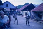 Adults and children gathered in the yard near buildings on a cocoa plantation in Trinidad