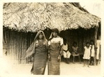 Photograph of two Guna women standing in foreground with children near a dwelling in the background.