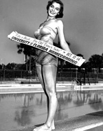 Arlo Godwin attired in a bathing suit holds a banner by Florida Pool for University of Florida Homecoming.