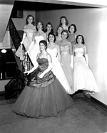 10 women in evening dresses pose on a staircase.