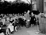 Dr. and Mrs. John J.Tigert stand while seated audience applauds at the dedication of Tigert Hall on the campus of the University of Florida.