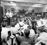 Three men with guitars and a large audience in Florida Union on the University of Florida campus