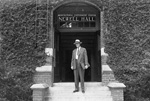 John J. Tigert, president of the University of Florida, standing on steps of the east entrance to Newell Hall.