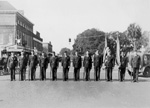 12 men in uniform stand in a line at attention on a street