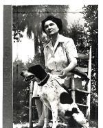 Marjorie Kinnan Rawlings seated outdoors with bird dog in Cross Creek