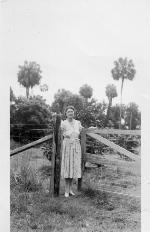 Marjorie Kinnan Rawlings standing at gate to her grove in Cross Creek