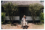 Norton Baskin, in front of the Rawlings house, flanked by two tea olive trees he planted in 1941